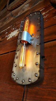 Wall sconce industrial light, Rivited lamp with edison bulbs. Steampunk décor.  For more interesting, custom, and unique signs and lights please visit: https://www.etsy.com/shop/HitandMissLimited?ref=l2-shopheader-name  This industrial wall sconce is made from 20ga steel with a riveted border and two tube type Edison bulbs. Each sconce is 20 1/2 tall and 7 wide, they hang from a loop on the backside at the top.  The light features a dimmer that also acts as an on/off switch and plugs in with…
