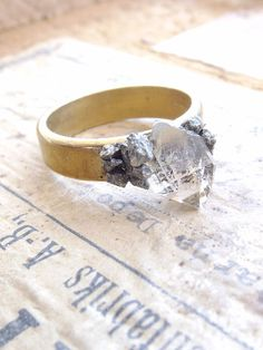 Shimmering raw pyrite arranged onto a antique brass ring and is accented with a lovely Herkimer Diamond point quartz.