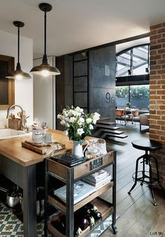 This is the cutest industrial kitchen I've ever seen. I love how the white flowers make it feel like a home.#industrial #industrialkitchen #brick #exposedbrick #brickkitchen #kitchenisland #butcherblock #whiteflowers #floatingstair #barstool #industriallight