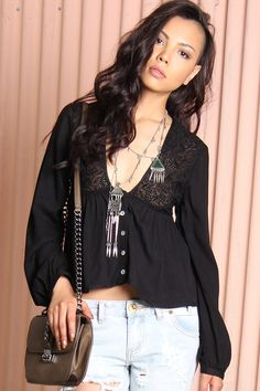 All-black flowing crop top by Somedays Lovin featuring an embroidered eyelet panel at the yoke with a button-up front and faux opal buttons. Finished with long sleeves and button cuffs. Looks perfect with distressed denim for a festival look.