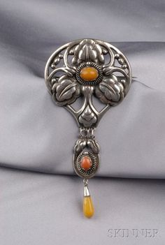 Kay Bojesen. Silver and Amber Brooch, Denmark, the floral form set with cabochon amber, suspending an amber drop, lg. 4 3/4 in., with maker's marks.