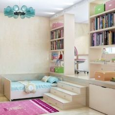 Teen shared bedroom with hidden beds under raised desk area, giving additional space to small kids room. Bright colors, lots of shelving bookshelves.