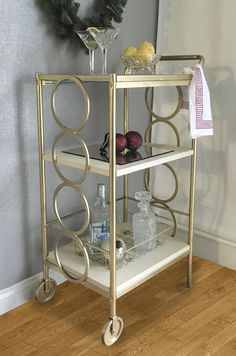 "Do you need a quick and easy diy bar cart for the holidays? Ikea Bygel Utility Cart, two Lola 7.5""x29.25"" x1/4"" O'verlay panels and a can of gold spray paint.  Paint, glue and decorate, that's all it takes."