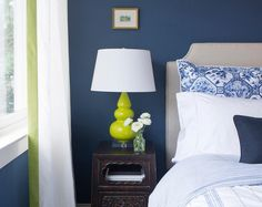 Beautiful bedroom features a bold blue wall lined with a gray headboard on bed dressed in blue bedding next to an antique Chinese nightstand topped with a neon green triple gourd lamp.