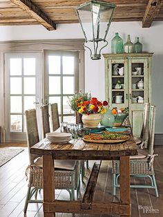 Pale blues and greens thread throughout this informal country-cabin eating area. The hushed palette, as well as pattern-free fabrics on seating, allows individual elements to emerge, including a 1700s lantern, rich farm-style table, and an antique cupboard bearing its original paint.
