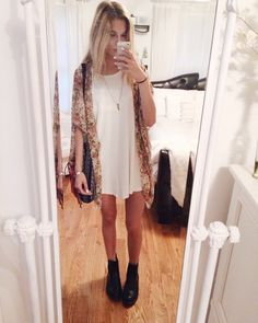 Cute girly boho look with the patterned kimono, flowy white dress, black boots, and a black shoulder bag.