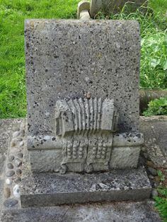 Tombstone of William 'Merry' Kimber of the Headington Morris side, known as Father of the Modern Morris - complete with his concertina and bell pads.