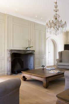 Serene Belgian living room:  paneled walls; coffee table; linen upholstered furniture, pine floors; arched pocket  doors; bare mantle (Lefevre Interiors)  Cabinets for upstairs/master