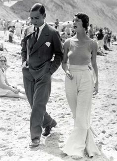 High-waisted, wide-legged, flared white trousers (linen?) with wrap around, fabric belt, worn with simple strappy top.  Dutch couple on the beach, c.1930s