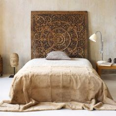 Concrete wall + carved headboard = divine and I like the shabby bedspread that ruffles on the floor.
