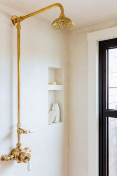 Lovely walk in shower is clad in stucco lined with a gold vintage exposed plumbing shower kit. Shower Floor, Walk In Shower, Master Shower, Bathroom Styling, Bathroom Lighting, Bathroom Inspo, Paris Bathroom, 1950s Bathroom, Gold Bathroom