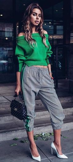 #spring #outfits woman in green off-shoulder sweater and gray pants with white pumps holding black handbag standing while looking straight to the camera. Pic by @streetstyle_belgrade