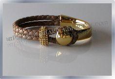 Base de pulseira dourada com  cabedal de cabra entrançado à mão. Conta com pedras brilhantes gravadas. ContaAgulhamagika_Ref. AM622