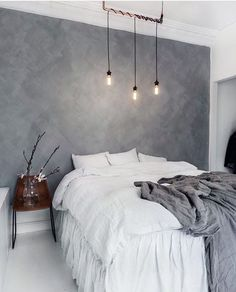 Edison lights, textured grey wall and white and grey bed