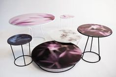 Moroso - Around the Roses  Around the Roses tables depict posies on digitally printed fabric embedded in acrylic. The tops range in hue from white and pink to violet and blue, and diameters measure 19¾ , 35½, or 43¼ inches. The varnished steel bases come in three heights with black or white lacquer
