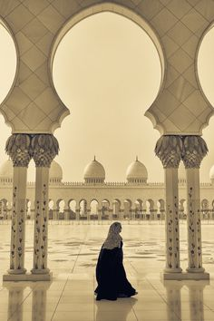 A woman walks along one of the arched passage ways in The Grand Mosque of Abu Dhabi in the Arab Emirates.