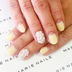 Brides.com: . A yellow half-moon manicure with white daisy nail art on the ring finger.