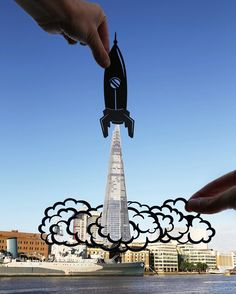 London-based photographerRich McCor, or paperboyo (previously) travels across the globe giving creative updates to buildings, bridges, and signs through the use of simple paper cutouts. By placing a black design in the foreground of his image, London's Tower Bridge is instantly transformed into a l
