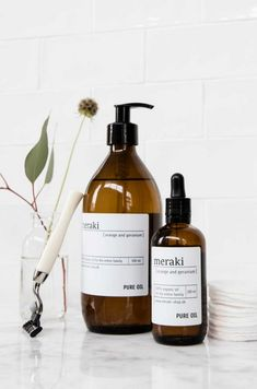 skin care large product bottles with pump and dropper, white subway tiles, white marble, eco razor blade, foliage