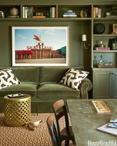 """""""With bright colors in other rooms, we wanted the husband's study to feel more serious and masculine,"""" says Weiss. The Charles Stewart Company sofa is in Dorian Bahr's Royal mohair, and the walls are painted in Benjamin Moore's Durango. The accent pillows are in Jed Johnson's L'Africain. Marlow drum stool and HD Buttercup. The patterned carpet is by Stark. - HouseBeautiful.com"""
