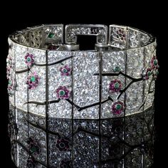 Art Deco era Cartier, circa 1925. It's a diamond strap bracelet with a really lovely design of gem-set cherry blossom branches and flowers.