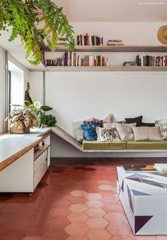 Prateleiras e sofás feitos de concreto e piso de hidráulico em formato hexagonal.