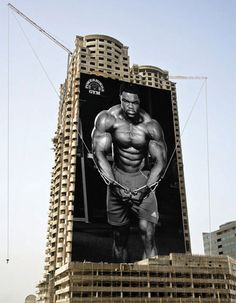 Powerhouse Gym Building Advertisement -  Creative advertisement campaign by Powerhouse Gym gives the impression that a body builder is lifting heavy weights from the construction site.