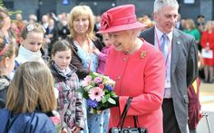 The Queen is presented with flowers during her visit to Orford Jubilee Park, Warrington