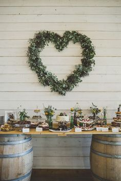 Whimsical wedding cake and dessert table display - like the idea of a green heart-shaped wreath #diy #dessert #weddingdessert #desserttable #weddingcake