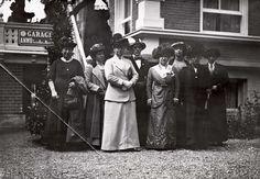 Vrouwenkiesrecht. Het hoofdbestuur van de Vereeniging van Vrouwenkiesrecht is bijeen in Apeldoorn. Acht sjieke dames, waaronder Wilhelmina Drucker en Aletta Jacobs, in lange japonnen of rokken, voor een gebouw te Apeldoorn, Nederland, 1913.