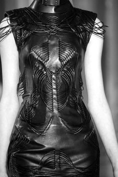 Black leather dress with structured cord patterns; dark fashion details