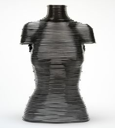 The corset is made of 97 handcrafted aluminium coils and has a 15-inch (22 cm) waist. The construction is similar to that of the cuirass (historical leather body armour designed for the torso in which the breastplate and backplate are fastened at the sides). In McQueen's version, the sides are screwed together, with the wearer inside. Kees van der Graaf created a plaster of Paris mould of model Laura Morgan's torso, onto which Leane then fitted the coils. Alexander McQueen Fall 1999