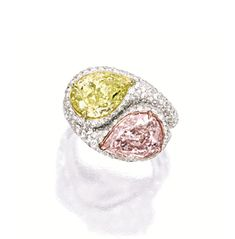 FANCY ORANGY PINK DIAMOND AND DIAMOND RING AND FANCY INTENSE YELLOW DIAMOND AND DIAMOND RING.  The first ring set with a pear-shaped fancy orangy pink diamond weighing 2.50 carats, decorated with circular-cut diamonds; the second ring of similar design, centring on a pear-shaped fancy intense yellow diamond weighing 3.01 carats; the diamonds altogether weighing approximately 2.60 carats, mounted in 18 karat white, yellow and pink gold. [Is this one ring or two?]