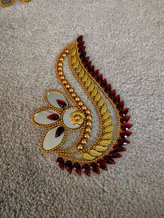 This is a set of beautiful handcrafted art pieces - one circular piece surrounded by 6 individual pieces - can be used as traditional floor decoration as Rangoli or can be wall mounted as art work. This is done on an acrylic sheet & the stones, mirrors, the other gold color decorative pieces are adhered well - it is a delicate looking but sturdy piece. The pieces can be arranged in different ways to change the finished look. Proceeds from sale of these go to an organization which trains &...