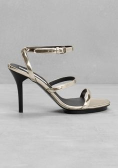 Dainty and sophisticated, these metallic-gold sandalettes feature thin straps and an ultra-feminine stiletto heel.