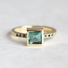 Green tourmaline ring with tiny black diamonds. A handmade engagement ring with a unique mint-aqua-green shade of tourmaline. ★Details Center stone: princess square mint green tourmaline Quality: VS clarity Weight: 0.75 - 0.9ct Measurements: approx. 5-5.5mm Setting: bezel Accent stones: round