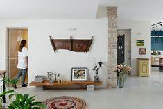 בחלק אחר שפתוח למרחב הסלון והמטבח נתלתה עבודת עץ שהובאה מאיטליה, ומתחתיה מדף נמוך מעץ מלא, שבמקום רגליים נתמך בערימות מגזינים. משמאל פינת העבודה של דינה שרון (צילום: גדעון לוין)