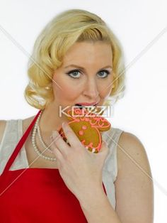 portrait of a young woman eating gingerbread biscuit. - Portrait of a young woman eating gingerbread biscuit against white background.