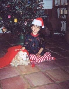 At our home, Tiffany with our dog Odie who is in heaven. She covered the dog with the cloth that covers bottom of Christmas tree. She wanted to keep him warm, so sweet. I love this pic.❥-Mari