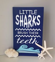 Navy Blue Little Sharks Brush Their Teeth wood sign This sign is perfect for a kids ocean themed bathroom. What a fun way to remind your kids to brush their teeth and have a cute piece of art in their bathroom. Approx 9.25x15 Colors may appear different depending on the computer or phone you are using. I am happy to customize colors, just let me know what you are wanting in the note to seller box. Thank you for viewing my listing. You can see more from my shop here https://www.etsy.com/s...