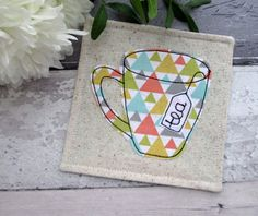 A geometric patterned fabric mug coaster, the perfect fabric gift for a tea lover!  The coaster features a mug with a tea bag tab which I have stitched the word tea onto. It is backed in a plain duck egg blue cotton fabric.  The coaster has cup/mug appliqued in 100% cotton fabric using free motion machine embroidery which allows me to draw freehand with the needle and thread on my sewing machine.  The coasters are interfaced for durability and can be washed at 40 degrees, so there is no…