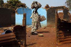 Een christelijke vrouw zoekt naar overblijfselen om mee te nemen tussen de resten van een huis in Bangui dat aan moslims toebehoorde.