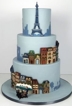 A Parisian themed wedding cake for a couple who got engaged at a cafe in Paris. All of the buildings are hand-sculpted out of modelling choc...