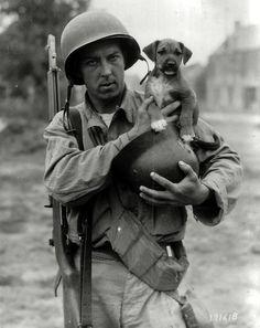 "Pfc Joseph E. Day holds a puppy named ""Invasion"" in a German helmet, Le Dezert, France, 1944 (via)"
