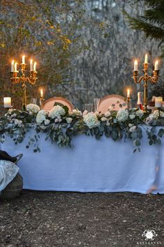 Romantic Outdoor Sweetheart Table - Kelley Nan -Head Table with Candelabras and Lots of Flowers and Eucalyptus Greenery in the forest for a wedding reception, anniversary, or Valentine's Day