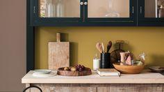 Okergele muur keuken combineren met HOUT, zacht oudroze, zachtgroen, grijstinten, goudtinten