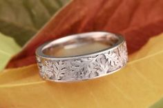 Oak Leaf Eternity Wedding Band. Layers of oak leaves in relief cover the surface of this wedding band. This nature-inspired ring can be made in the precious metal and width of your choice.