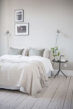 Minimalist bedroom with gray hues, simple bedding, and a simple black nightstand