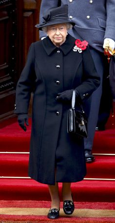 2014 Queen Elizabeth attended the annual Remembrance Sunday Service in London wearing a black coat (featuring a remembrance poppy detail) and hat.