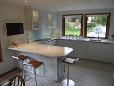 High Gloss White units topped with Light Ash Corian, finished with a glass splashback in Teal. #German #Kitchens #White #Gloss #GlossWhite #Corian #LightAsh #Glass #Splashback #Teal